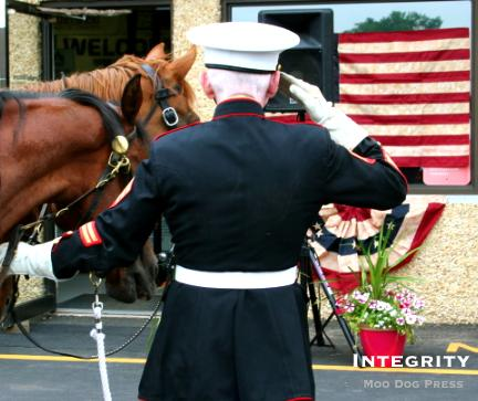 Combat veteran U.S. Marine Rick Kowalker, hand on horse, snaps a salute in a ceremony that involved his horse trailer presentation.